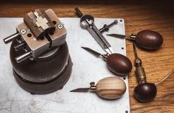Juwelier ` s workplase mit Werkzeugen und Kreuz im Bullaugenkolben Stockfotos