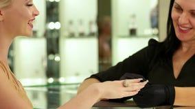 Juweliergeschäft, goldener Ring mit Diamanten, glückliche Frau, die mit lächelndem Verkäufer im Schmuck, Wahl des Goldschmucks sp stock video