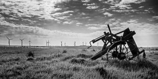 Old and new technology - wind turbines and abandoned plough - black and white Stock Photo