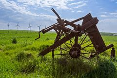 Old and new technology - wind turbines and abandoned plough Stock Photos