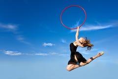 Jymnast con el aro que salta contra el cielo azul Imagen de archivo libre de regalías