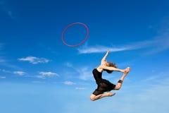 Jymnast con el aro que salta contra el cielo azul Imagenes de archivo