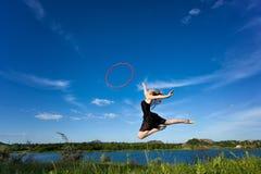 Jymnast con el aro que salta contra el cielo azul Fotografía de archivo
