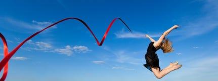 Jymnast con la cinta roja que salta contra el cielo azul Imagen de archivo libre de regalías