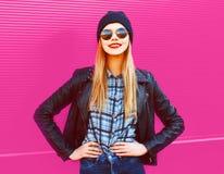 Kühles blondes lächelndes Mädchen des Porträts in der Felsenschwarz-Artjacke, Hut, der auf Stadtstraße über bunter rosa Wand aufw lizenzfreie stockfotos