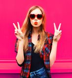 Kühles Mädchen des Porträts in der geformten Sonnenbrille des Herzens, die süßen Luftkuß auf buntem Rosa sendet lizenzfreies stockfoto