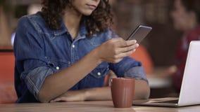 Kędzierzawy z włosami kobiety gawędzenie na smartphone przy stołem z laptopem i filiżanką herbata zdjęcia royalty free