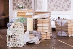 Käfig mit Vögeln und alte Bücher häufen in der Innenausstattung Stockfotos