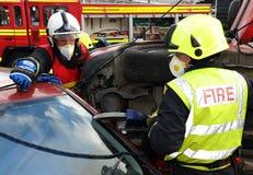 Käkar för brandservice av livklipp på en bilkrasch Arkivbild