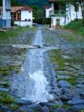 Källan av rent vatten på en sten stenlade vägen med den suddiga staden i bakgrundslodlinjen arkivbild