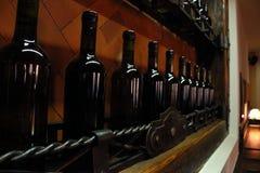 Källaren bordlägger med mörker korkade vinflaskor mot ljus - brun trävägg Royaltyfria Foton