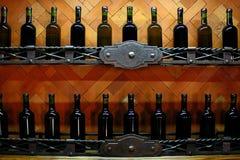 Källaren bordlägger med mörker korkade vinflaskor mot ljus - brun trävägg Royaltyfria Bilder