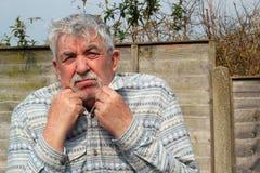 Kälte des älteren Mannes, versuchend, warm zu halten. Stockbilder