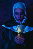 Kälte tont Porträt des weiblichen Mönchs mit Kerze in den Händen Stockbilder
