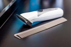 Kämmen Sie und eine Haarschnittmaschine im Friseursalon auf Vorlagen-` s table_ lizenzfreie stockbilder