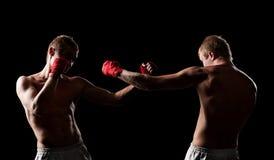Kämpar som boxas i darken fotografering för bildbyråer