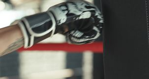 Kämpe som öva några sparkar med den stansa påsen - en kvinnaboxning på bakgrund Den svarta stansa påsen väger på idrottshallen lager videofilmer