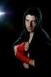 Kämpeman i boxninghoodieförkläde med huven på det isolerade huvudet med handen och handled slåget in klart för att slåss att pose Royaltyfri Foto