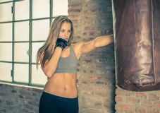 Kämpeutbildning kvinna som stansar den tunga påsen för boxning Fotografering för Bildbyråer