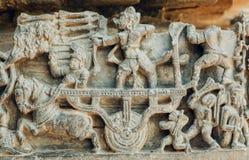 Kämpfende Szene mit Armee von alten Soldaten Grafik 12. centur Hoysaleshwara-Tempels in Halebidu, Indien Stockfoto