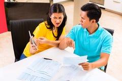 Kämpfende unbezahlte Rechnungen der asiatischen Paare Lizenzfreie Stockbilder