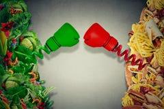 Kämpfende ungesunde Fertigkost des vegetarischen Lebensmittels mit den Boxhandschuhen, die e lochen Stockfotografie