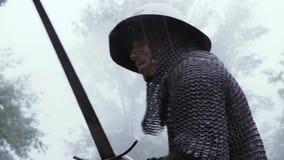 Kämpfender mittelalterlicher Soldat in chainmail Rüstung und Sturzhelm, seine Klinge schwingend stock video