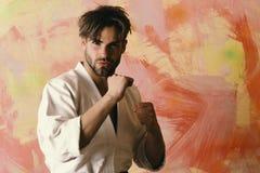 Kämpfer, der Karateposition auf farbigem Hintergrund durchführt Verteidigung und Taekwondo-Sportkonzept stockfotografie