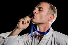 Kämpfer, der seine Goldmedaille küsst Lizenzfreies Stockfoto