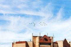 Kämpfer und Kampfflugzeuge im Himmel über Haus Stockfoto