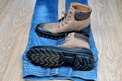 Kängor för läder för man` s på jeans Arkivfoton