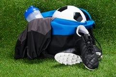 Kängor, fotbollbollen, T-tröja och en vattenflaska, i sportar hänger löst, mot bakgrunden av gräs arkivfoton