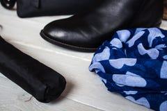 Kängor halsduk och paraply på träbakgrund Arkivbild