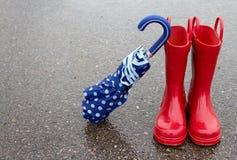 kängor rain det röda paraplyet fotografering för bildbyråer
