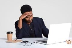Känner sig den mörka flådde orakade mannen för trött trötthet överansträngd efter lång tid som arbetar, håller handen på pannan,  arkivfoto