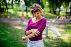 Känsla för den unga kvinnan smärtar i hennes armbåge, hand under sportgenomkörare arkivbilder