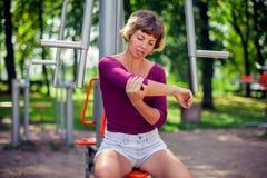 Känsla för den unga kvinnan smärtar i hennes armbåge, hand under sportgenomkörare arkivfoto