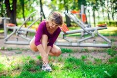 Känsla för den unga kvinnan smärtar i hennes fot under sportgenomkörare i royaltyfri fotografi