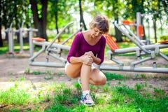 Känsla för den unga kvinnan smärtar i hennes knä under sportgenomkörare i royaltyfria bilder