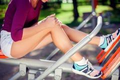 Känsla för den unga kvinnan smärtar i hennes knä under sportgenomkörare i royaltyfria foton
