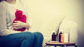 Känsliga magekramper för kvinna som sitter på cofa Royaltyfria Bilder