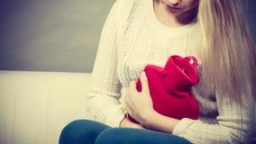 Känsliga magekramper för kvinna som sitter på cofa Arkivbild
