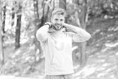 Känsligt bekvämt Skäggig attraktiv tillfällig satt huv för grabb på Man med borstet som ler framsidanaturbakgrund royaltyfri foto