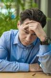 Känsligt trött på Frustrerad ung man som håller ögon stängda, medan sitta på hans arbetsplats i regeringsställning arkivbilder