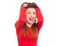 Känslomässigt stressad kvinna i rött gripa hennes isolerade hår Arkivfoton
