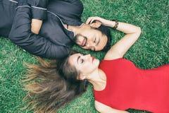 kärlekshistoria för trädgårds- flicka för pojke kyssande En brunettman och en härlig brunettkvinna ligger på gräset arkivfoto