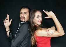 Kärlekshistoria-, man- och kvinnabrunetter på en svart bakgrund Ett par som poserar som herr och fru smed royaltyfri foto