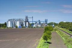 Kärnar ur metalliska silor för korn av hissen och växten med järnväg för sändning i fältet av vårfält fotografering för bildbyråer