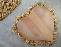 Kärnavalnöten är i rad omkring hjärta-format trä på säckväv arkivfoton