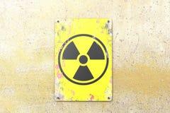 K?rnkraftsanl?ggning tecken som h?nger p? en gul v?gg Indikering av n?rvaron av ett radioaktivt omr?de royaltyfri illustrationer